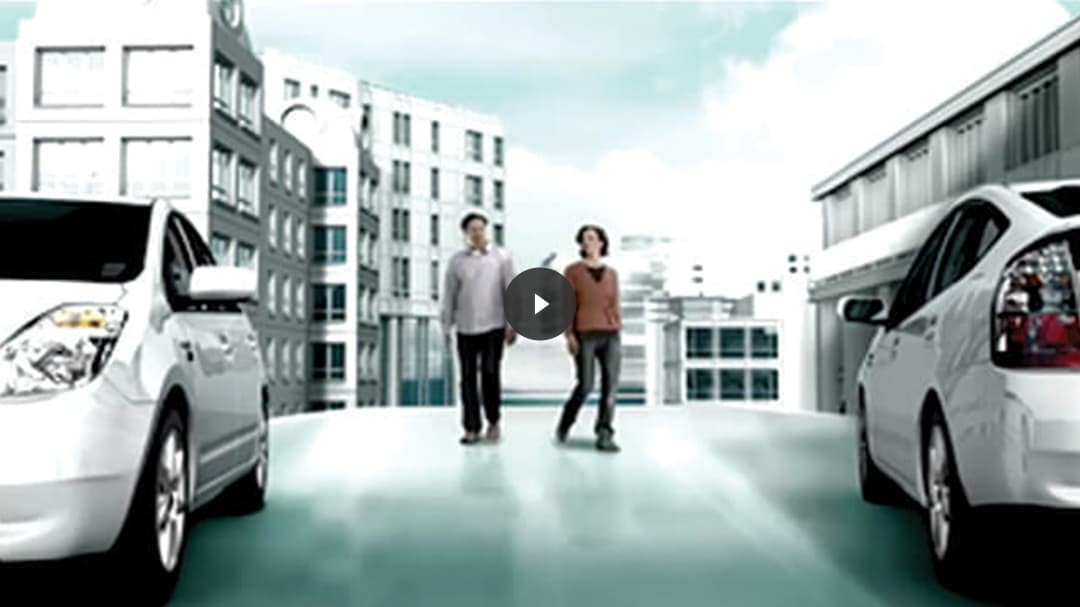 Two people walking between two Prius vehicles overlaid with video play thumbnail